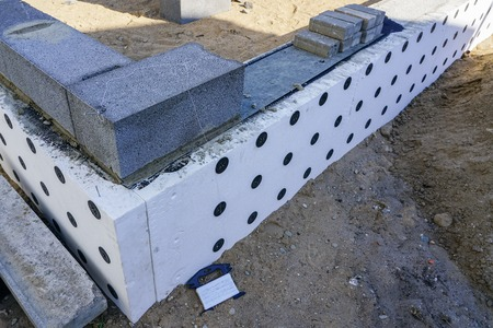 Concrete foundation and foundation thermal insulation of a new house, view of construction site in preparation process