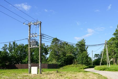 wooden power line pole with electric transformer in rural area, blue sky background