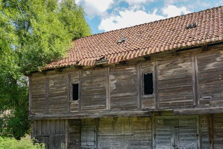 old abandoned wooden house with a crumbling clay roof against a blue sky