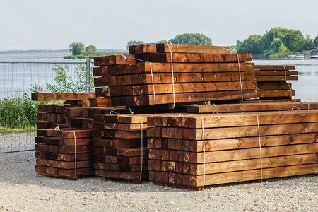 una pila de madera impregnada lista para la construcción de una casa de madera moderna Foto de archivo