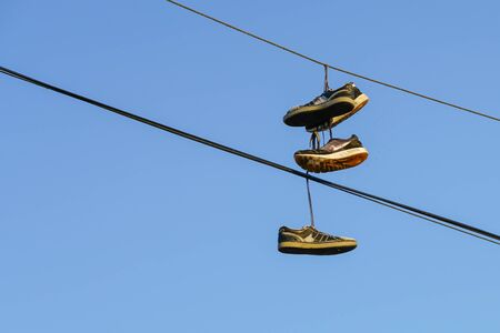 Several tennis shoes on power lines in front of a clear blue sky.