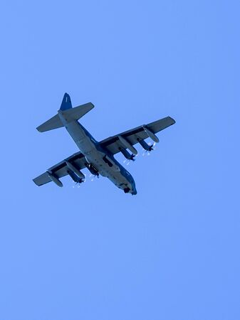 grey military transport plane fly on blue sky background
