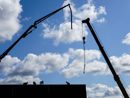 elevated crane booms on a construction site, against a blue sky