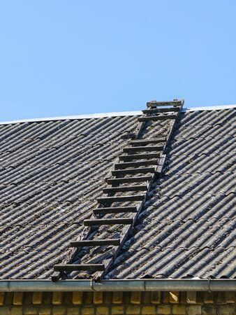old wooden ladder on slate roof with blue sky in background