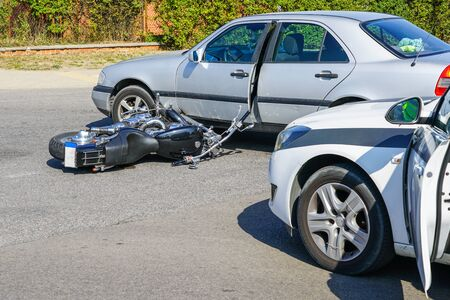 traffic accident, motorcycle collision with a car on city street, overturned motorcycle Stock Photo
