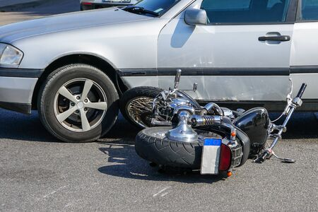 traffic accident, motorcycle collision with a car on city street, overturned motorcycle 版權商用圖片