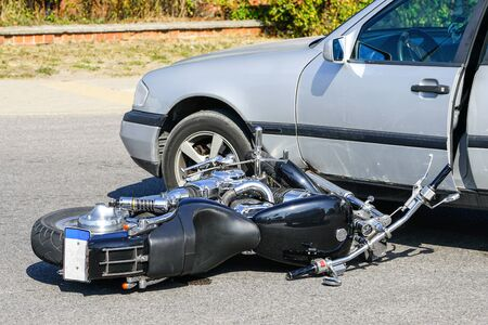traffic accident, motorcycle collision with a car on city street, overturned motorcycle Stockfoto