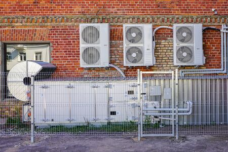 new air ventilation and air conditioning units outside an old brick house Imagens