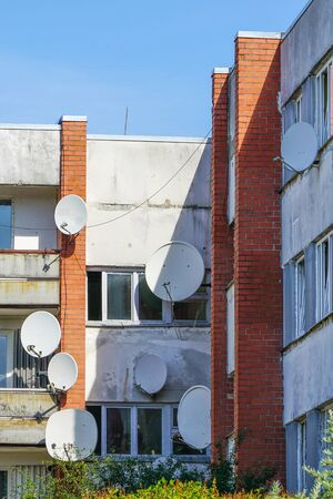 many white parabolic satellite antena dishes hanged on wall of suburban perfab block of flats. Wireless television broadcasting reciever. Zdjęcie Seryjne