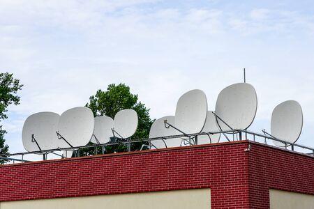 many white parabolic satellite antena dishes on the roof of the house