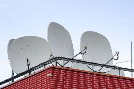 de nombreuses antennes paraboliques blanches sur le toit de la maison