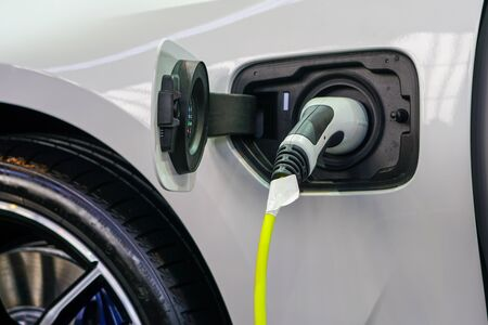 The electric car charger plugged in to the socket, the modern electric car charging the battery