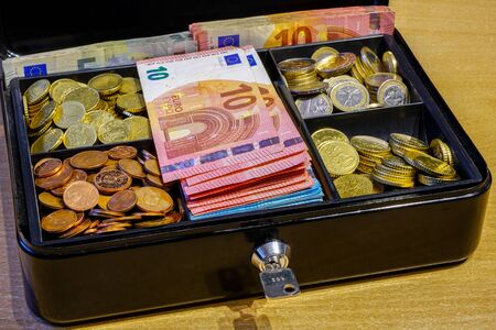 a small cash box full of coins and many banknotes