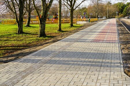 new paved walkway with bicycle lane and with guidelines for visually impaired people Stockfoto