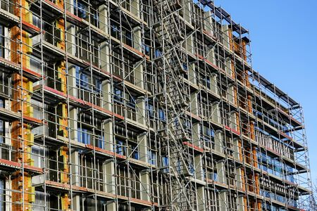 scaffolding arround the house to install thermal insulation of the building facade, workers in safety vests and helmets Stock Photo