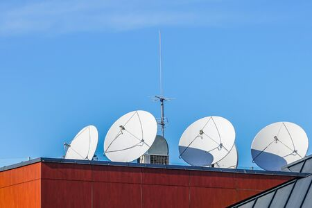 many white parabolic satellite antena dishes on the roof of the house. Wireless television broadcasting recievers