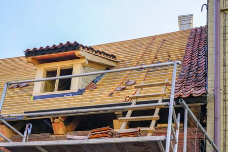repair of the roof structures of a beautiful historic wooden house and replacement of clay tiles Standard-Bild