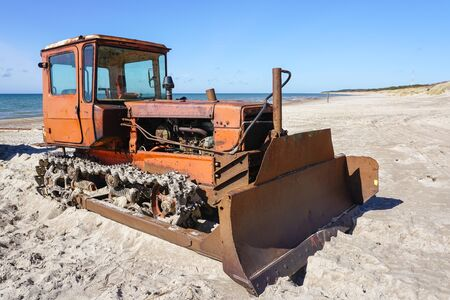 heavy bulldozer as fishing boat puller on the sand at the seashore 스톡 콘텐츠