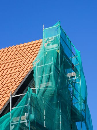 restoration of a historic wooden house, facade repair and replacement of roof clay tiles