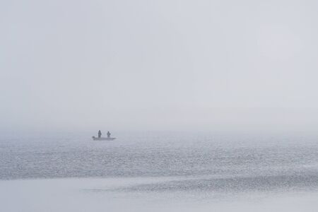 view of the lake and a boat with anglers in the fog