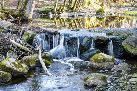 beautiful view of a waterfall in a small river in a wooded area