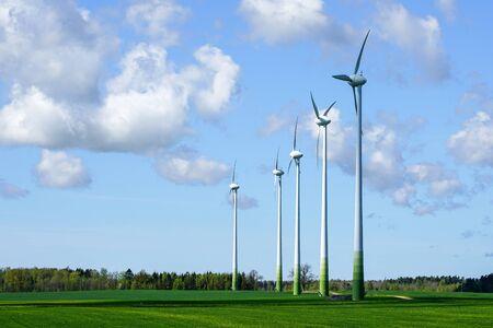 five wind turbine masts in a green field on a blue sky background
