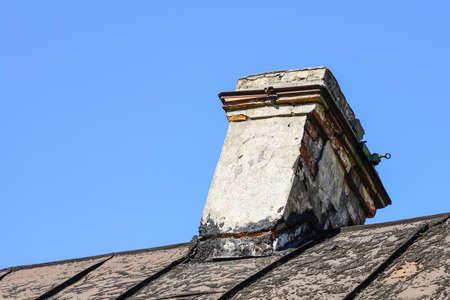 damaged brick chimney, cracked and dangerously skewed 写真素材