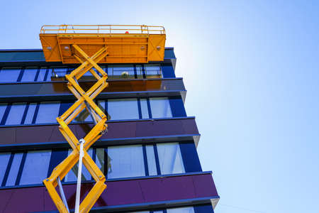 modern building facade repair using a high scissor lift with a platform