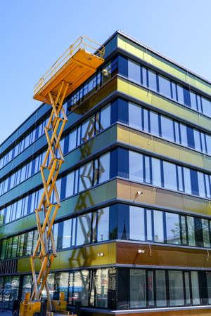 modern building facade repair using a high yellow scissor lift with a platform Imagens