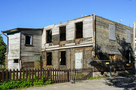 an old abandoned two-storey wooden house on a city street under demolition stage Stock Photo
