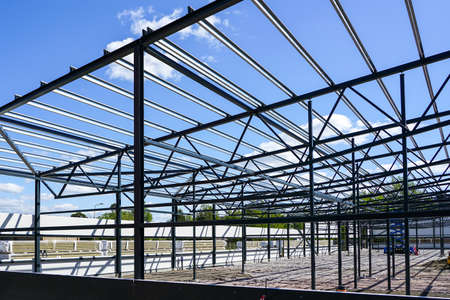 construction of a new modern industrial building, metal truss frame on a background of blue sky Stockfoto