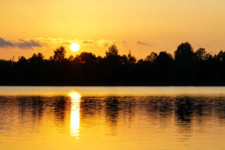 beautiful view of the lake at sunset, trees and sun reflection in the water