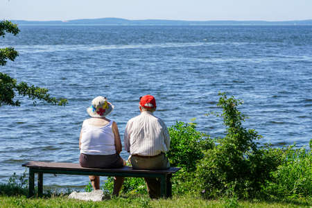 old woman and man sitting on a bench by the sea and looking into the distance, rear view