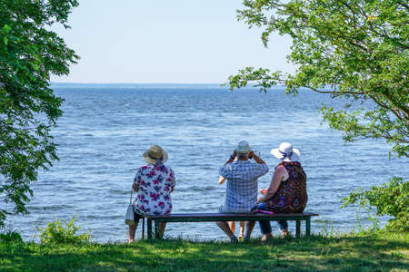 an two old womans and a man sit on a bench by the sea and look into the distance, rear view 免版税图像