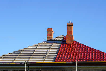 replacement of the roofing of a residential house on a background of blue sky, half changed, half not yet Stock fotó