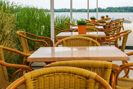 idyllic empty alfresco cafe by the lake with wicker chairs and tables with greenery pots