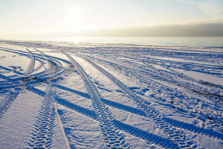 car and quad bike tire footprints on a snow covered beach at sunset 版權商用圖片