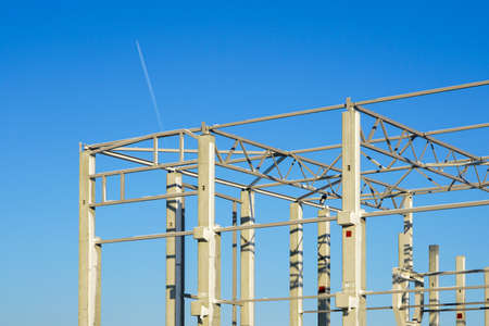 a fragment of the frame of a new modern factory reinforced concrete structure building on a blue sky background