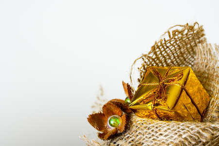 one small golden gift box with golden ribbon on burlap base, light background Stock fotó