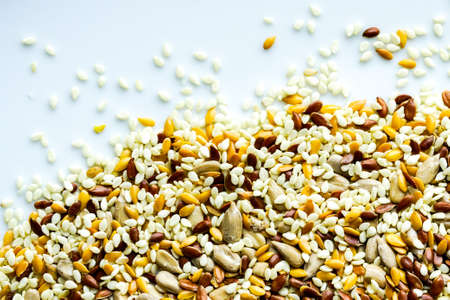 a mixture of sunflower seeds, linseed and sesame seeds on a white background