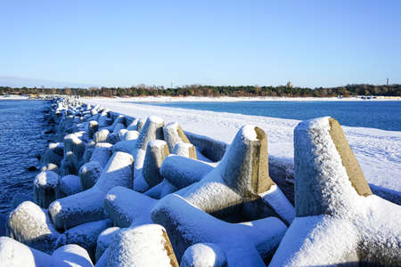 winter seascape, port entrance with snow covered concrete tetrapods breakwater 版權商用圖片