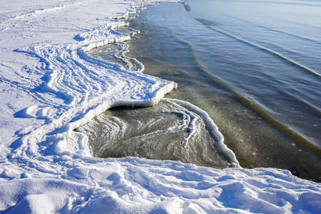 winter on the Baltic coast, snow, ice and water form the shoreline