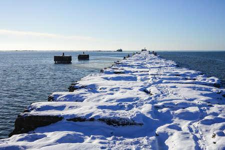 winter seascape, port entrance with snow covered concrete blocks breakwater Stock fotó