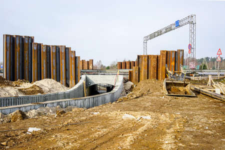 construction of a pedestrian tunnel under the highway, temporary metal retaining wall support the foundation
