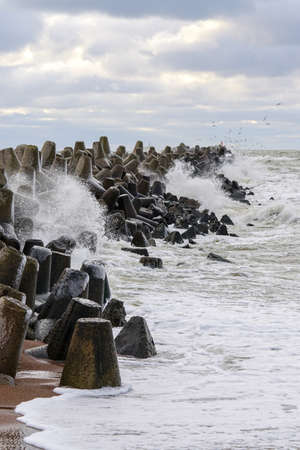 storm on the Baltic sea coast, waves hitting the breakwater concrete tetrapods