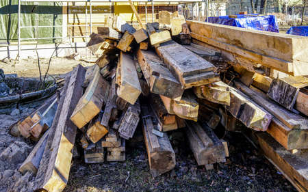 a pile of used wooden building materials for reuse in a wooden house restoration site 版權商用圖片