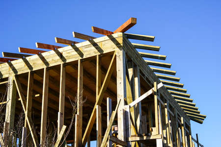new modern wooden house frame under construction, blue sky background