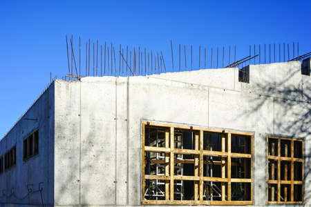 a wall of a new modern house built using concrete formwork on a blue sky background