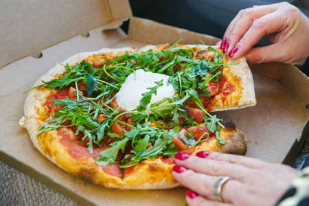 a woman sits in a car and tears pizza with burrata cheese and greens with red lacquered nails Stock fotó