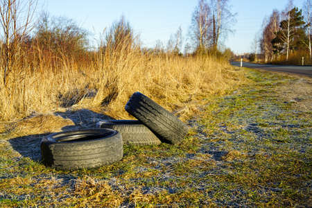 used car tires dropped on the side of the road, precedent for nature pollution Reklamní fotografie